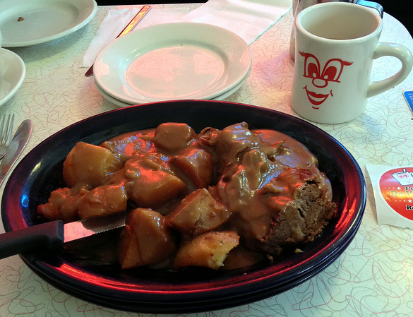 Fork tender pot roast served with roasted potatoes and carrots then drowned in homemade gravy at The Red Arrow Diner